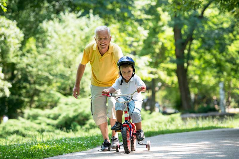 grandparent helping grandson ride bike