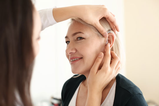 Audiologist fitting a hearing aid on woman's ear