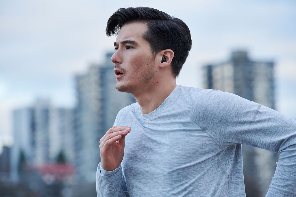 Man running with black custom hearing aid